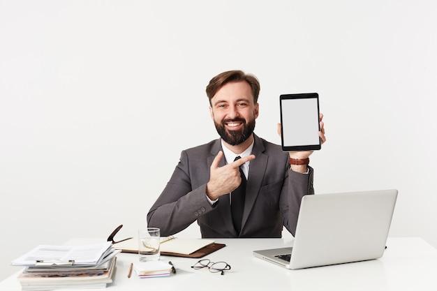 Wesoły przystojny młody brunet z brodą ubrany w formalne ubrania na białej ścianie, siedząc przy stole z tabletem w uniesionej ręce, szczęśliwie patrząc do przodu z szerokim uśmiechem