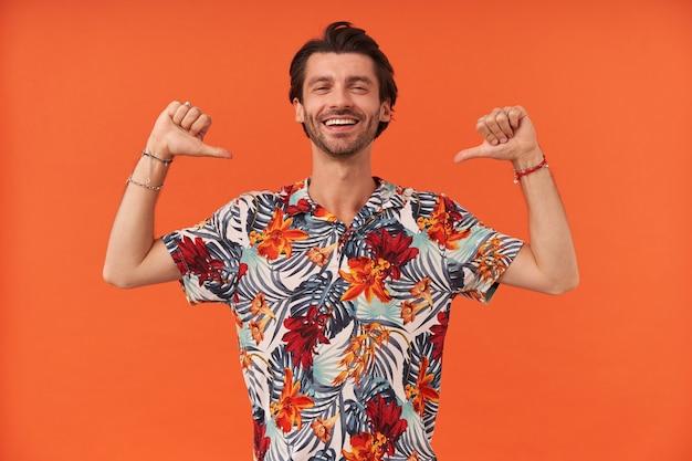 Wesoły przystojny młody człowiek z włosiem w hawajskiej koszuli wygląda pewnie i wskazuje na siebie dwoma kciukami
