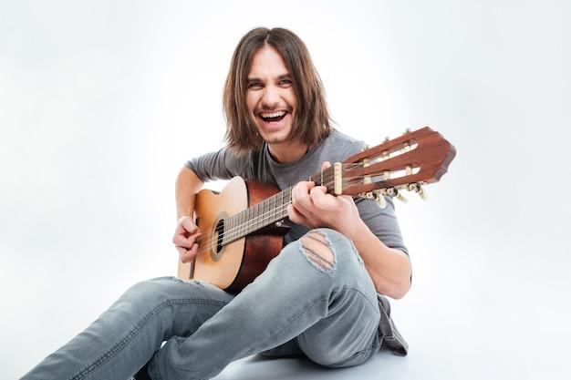 Wesoły przystojny młody mężczyzna z długimi włosami siedzi i gra na gitarze na białym tle