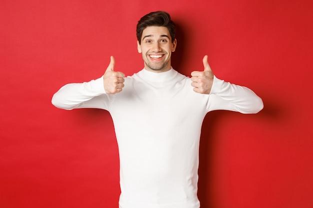 Wesoły, przystojny model w białym swetrze, pokazujący kciuki do góry z aprobatą, jak coś dobrego, stoi na czerwonym tle i uśmiecha się zadowolony.