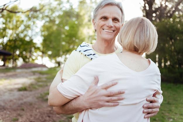 Wesoły przystojny starszy mężczyzna wyrażający miłość, ciesząc się rodzinnym weekendem i przytulając swoją żonę