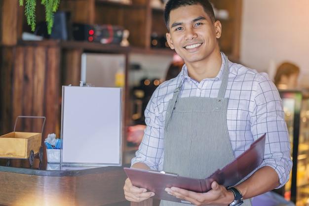 Wesoły przystojny właściciel firmy stojącej z zapraszam obecne menu przed barem.