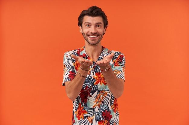 Wesoły radosny młody człowiek z zarostem w kolorowej koszuli, trzymając i dając coś na puste dłonie do aparatu