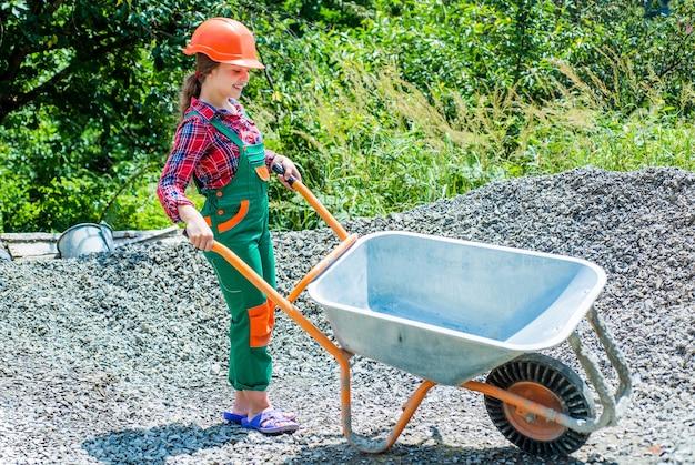 Wesoły robotnik dziecięcy za pomocą munduru budowlanego i taczki budowlanej, przyszła kariera.