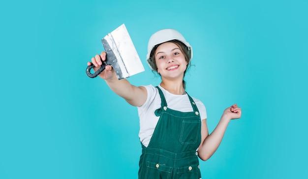 Wesoły robotnik używający munduru budowlanego i szpachelki do tynkowania, dzień pracy.