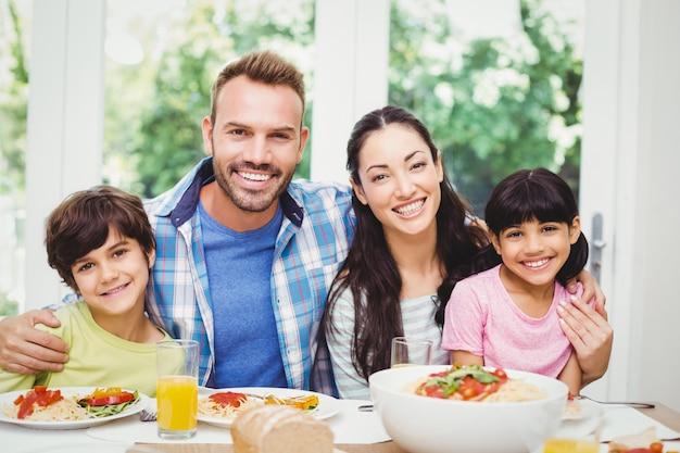 Wesoły rodzice i dzieci przy stole jadalnym