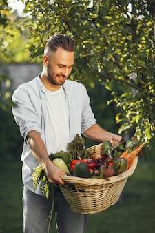 Wesoły rolnik z ekologicznymi warzywami w ogrodzie. mieszane organiczne warzywa w wiklinowym koszu.