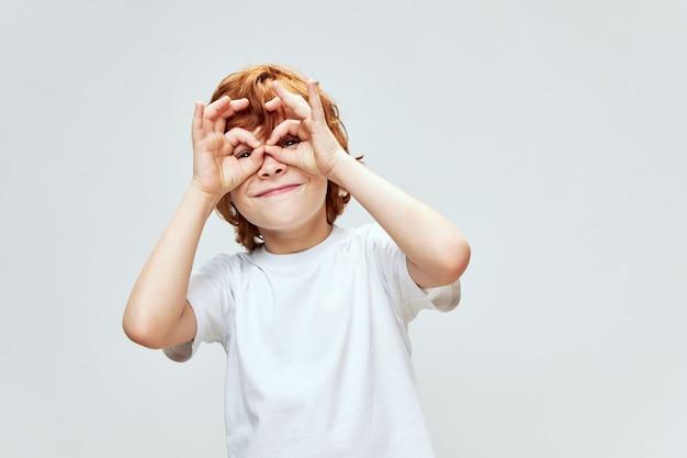 Wesoły rudowłosy chłopak trzymając się za ręce może twarze w postaci maski uśmiech radości z dzieciństwa