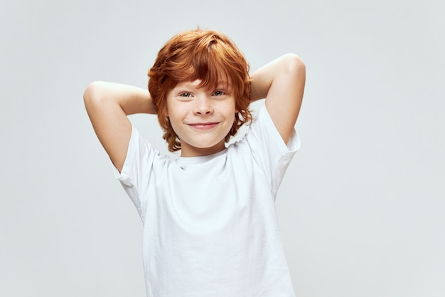 Wesoły rudowłosy chłopak trzymając się za ręce za głową uśmiech biała koszulka szara na białym tle ściana
