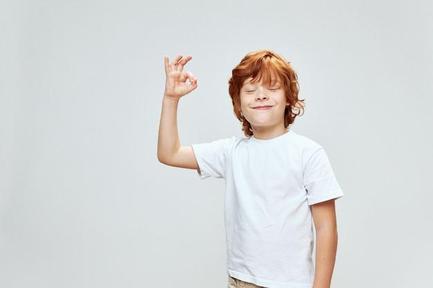 Wesoły rudowłosy chłopiec gestykuluje ręką uśmiechem zamknięte oczy biała koszulka studio