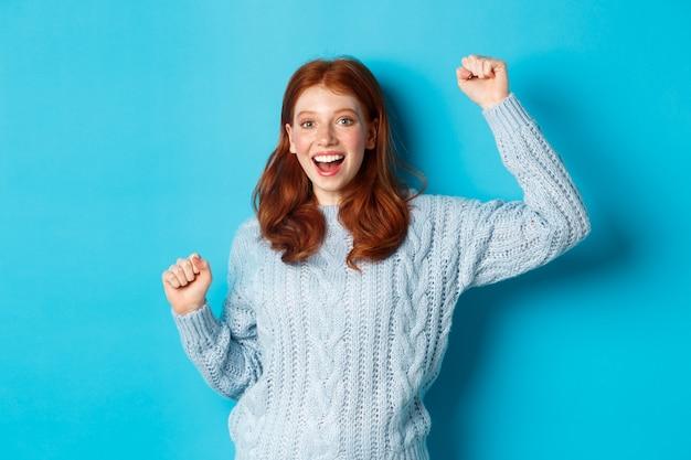 Wesoły rudowłosy gil wygrywający, świętujący zwycięstwo, uśmiechający się i skaczący ze szczęścia, pozujący na niebieskim tle.