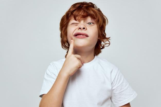 Wesoły rudy chłopiec trzymając rękę w pobliżu twarzy uśmiech przycięty widok biała koszulka szare tło