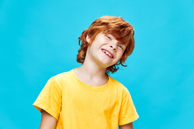 Wesoły rudy dziecko uśmiecha się na białym tle