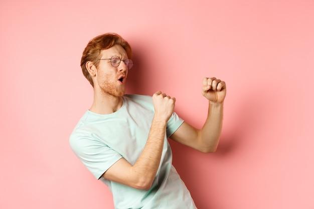 Wesoły rudy facet słucha muzyki i tańczy, triumfuje lub świętuje sukces, stojąc na różowym tle.