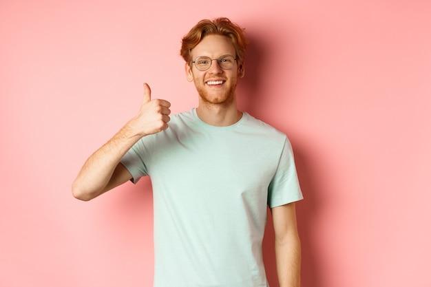 Wesoły rudy mężczyzna w okularach i t-shircie, pokazujący kciuki do góry z zadowoloną miną, pokazujący pozytywną reakcję, aprobuje i zgadza się z tobą, stoi na różowym tle.