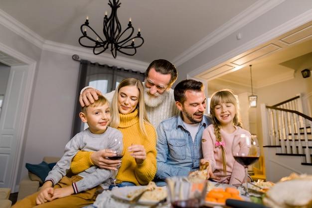 Wesoły siwowłosy dziadek, wnuki, rodzice siedzą przy stole, jedzą pyszne pyszne jedzenie i dobrze się bawią