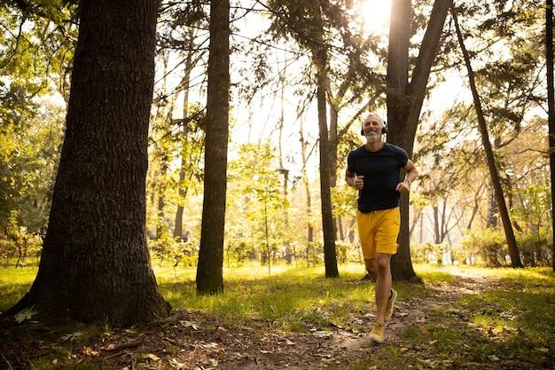 Wesoły siwy mężczyzna biegający w słonecznym lesie