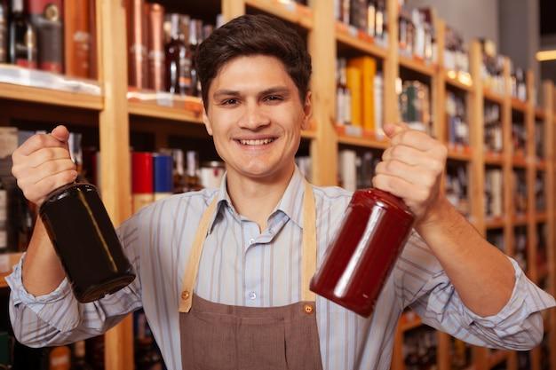 Wesoły sklepikarz uśmiecha się do kamery, trzymając dwie butelki whisky. z podnieceniem młody człowiek cieszy się pracować przy jego sklepem monopolowym