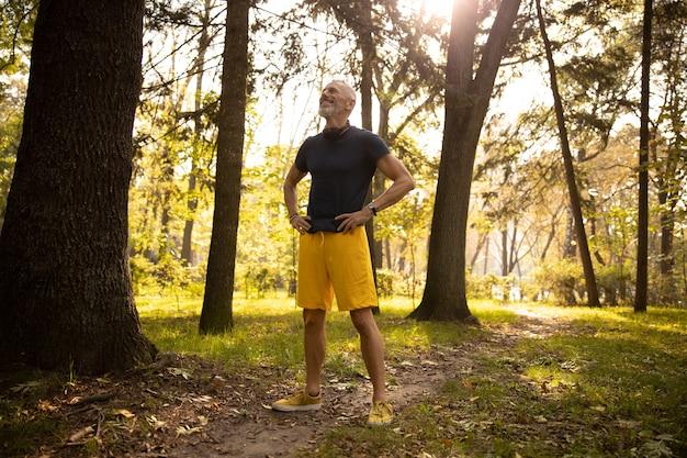 Wesoły sportowy facet spędzający czas na łonie natury