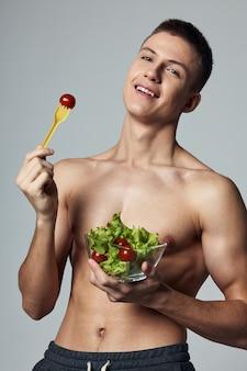Wesoły sportowy facet z nagim torsem z sałatką zdrowej żywności