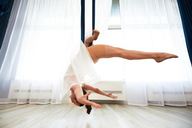 Wesoły sportowy kobieta ubrana w top i legginsy, wykonując antygrawitacyjne ćwiczenia jogi w przestronnym klubie fitness.