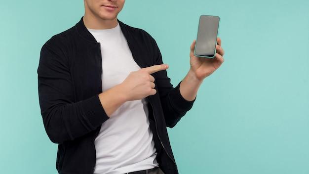 Wesoły sportowy rudowłosy facet pokazuje palcem na ekranie smartfona