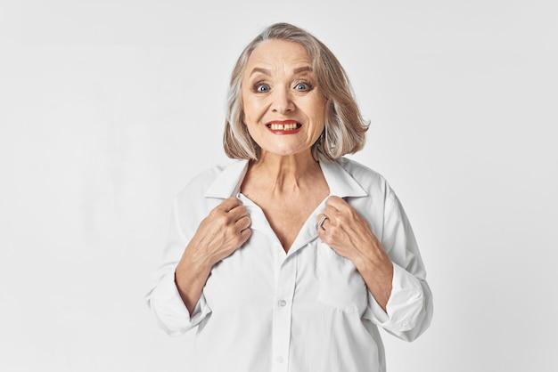 Wesoły starsza kobieta w białej koszuli emocje studio styl życia. zdjęcie wysokiej jakości