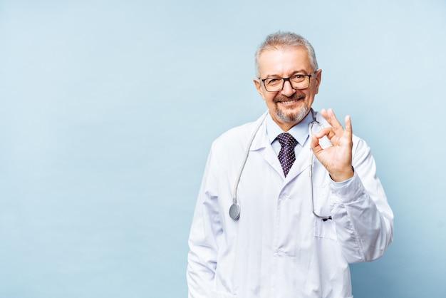 Wesoły starsze lekarz pozowanie i uśmiecha się do kamery, opieki zdrowotnej i medycyny lekarz pokazuje ok