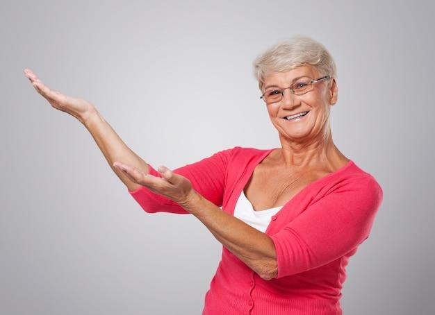 Wesoły starszy kobieta pokazując w przestrzeni kopii