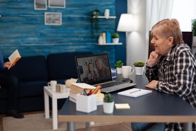 Wesoły starszy kobieta rozmawia z wnuczką podczas wideokonferencji. szczęśliwa babcia komunikująca się z rodziną za pośrednictwem internetowej wideokonferencji internetowej z wykorzystaniem nowoczesnej technologii internetowej