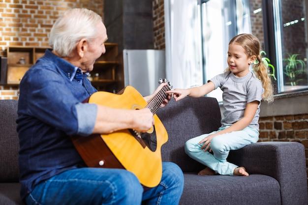 Wesoły starszy mężczyzna gra na gitarze dla swojej uśmiechniętej wnuczki w domu