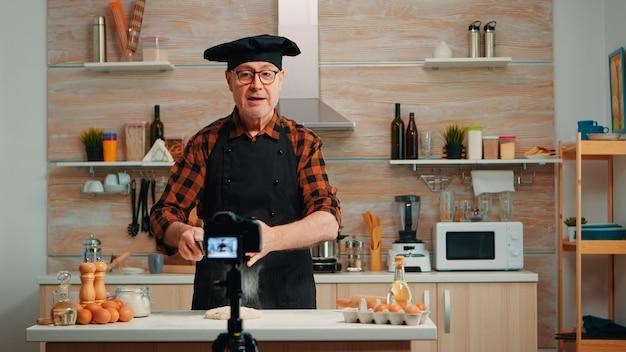 Wesoły starszy mężczyzna piekarz filmowanie vlog gotowania w domowej kuchni. emerytowany bloger, wpływowy szef kuchni, korzystający z komunikacji internetowej, kręcenia blogów w mediach społecznościowych za pomocą sprzętu cyfrowego