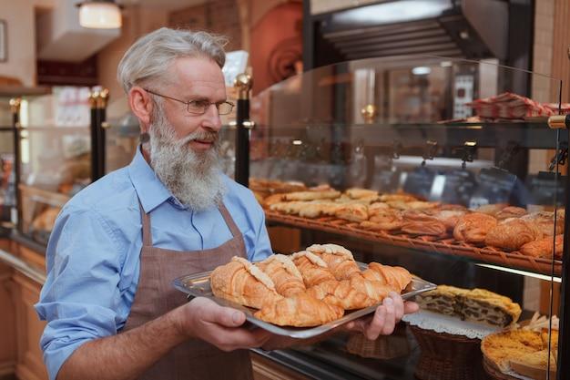 Wesoły starszy mężczyzna piekarz niosący rogaliki do pieczenia w swojej piekarni