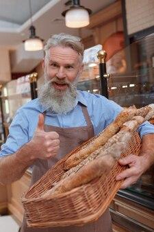 Wesoły starszy mężczyzna piekarz pokazując kciuk do góry, trzymając bochenki chleba w koszu