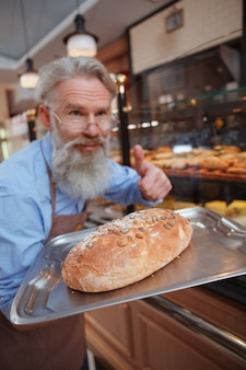 Wesoły starszy mężczyzna piekarz pokazując kciuk do góry wyciągając świeży chleb do kamery