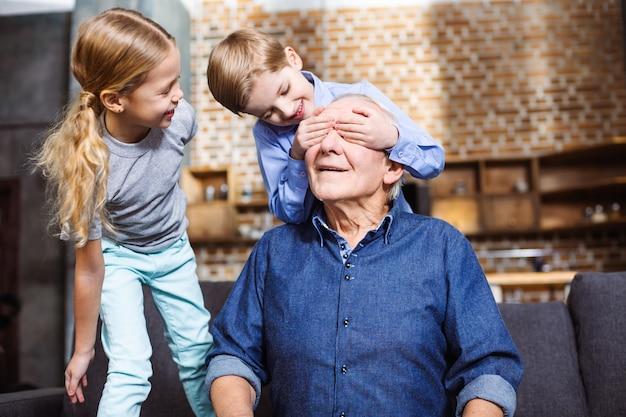 Wesoły starszy mężczyzna siedzi na kanapie, podczas gdy jego małe wnuki zamykają oczy