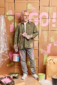 Wesoły starszy mężczyzna trzyma wiadro z farbą i pędzel sprawia, że naprawy wyglądają na radośnie ubrany w zwykłe ubrania, zajęty remontem w domu. koncepcja konserwacji ulepszenia domu przebudowy