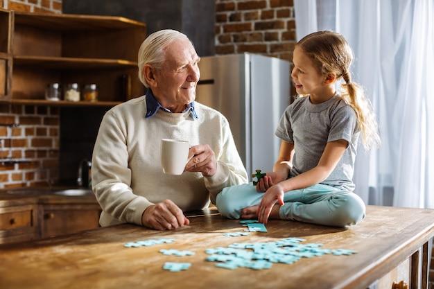 Wesoły starszy mężczyzna układa puzzle ze swoją wnuczką, odpoczywając w domu