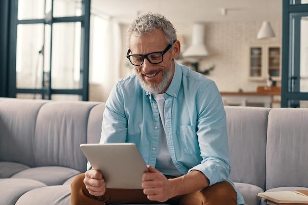 Wesoły starszy mężczyzna w codziennej odzieży przy użyciu cyfrowego tabletu siedząc na kanapie w domu