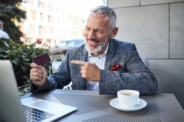 Wesoły starszy mężczyzna wskazujący na ciemnoczerwoną kartkę w dłoni i uśmiechający się w trakcie wideorozmowy