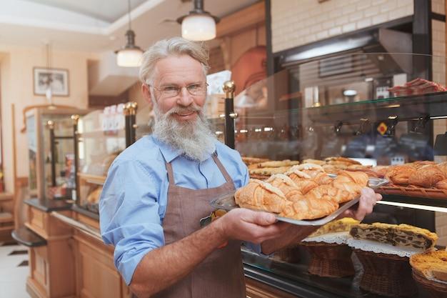 Wesoły starszy piekarz uśmiecha się do kamery niosąc pyszne rogaliki