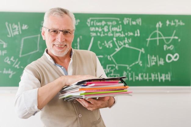 Wesoły starszy profesor trzyma stos notebooków w sali wykładowej