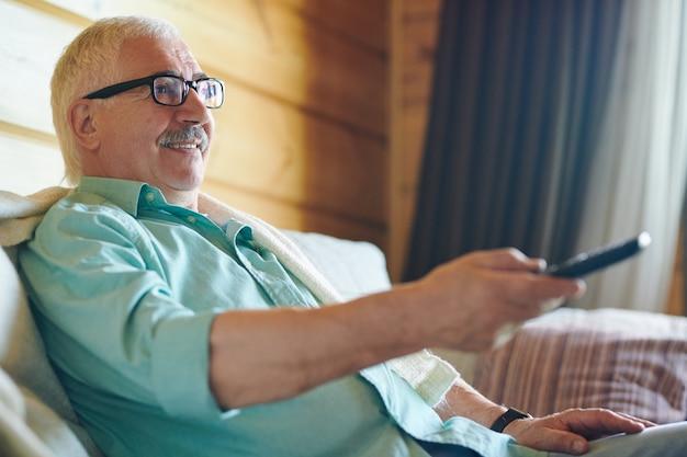 Wesoły starszy siwy mężczyzna w okularach i koszuli siedzi na kanapie i przełącza kanały telewizyjne, decydując, co oglądać