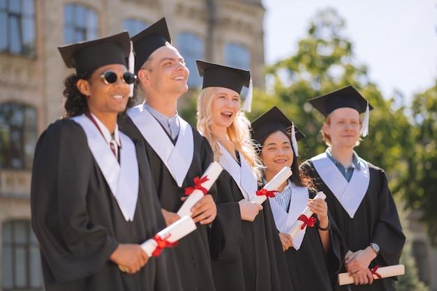 Wesoły studenci w sukniach ukończenia szkoły stoją obok siebie
