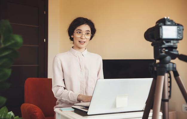 Wesoły student kaukaski, który podczas kwarantanny prowadzi lekcję online przy użyciu laptopa i nowoczesnego aparatu fotograficznego