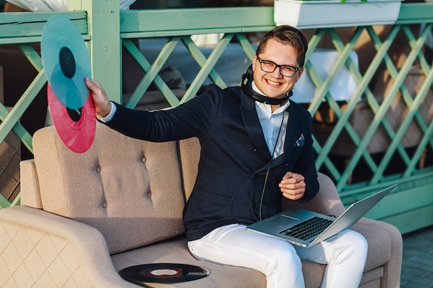 Wesoły stylowy facet ze słuchawkami i laptopa na swoim kness trzyma płytę winylową poza