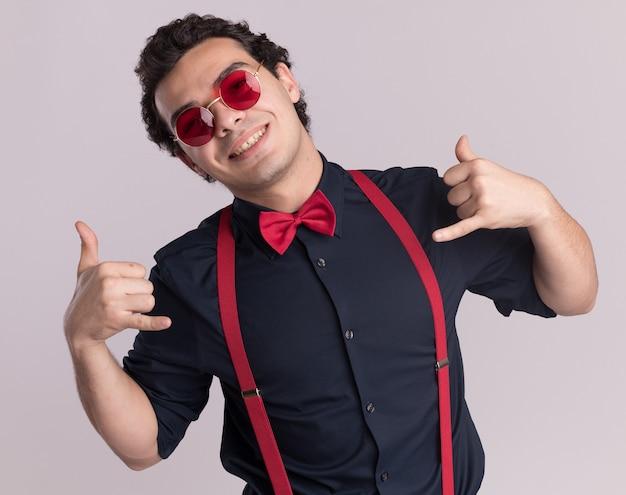 Wesoły stylowy mężczyzna z muszką w okularach i szelkach patrząc na przód uśmiechnięty pokazujący zadzwoń do mnie gest stojący na białej ścianie