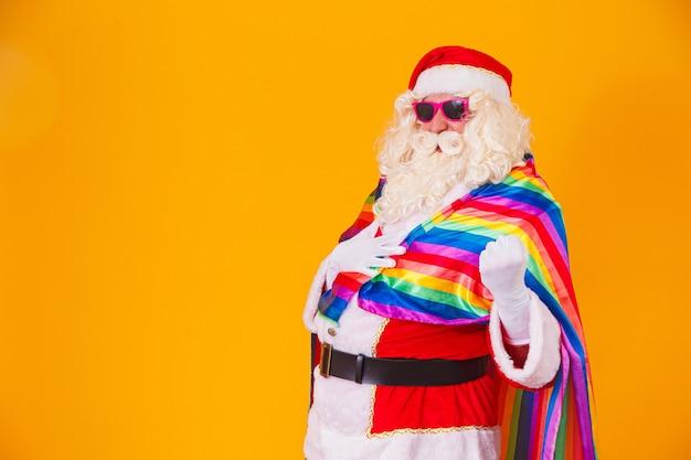 Wesoły święty mikołaj trzymający flagę lgbt. boże narodzenie gay pride concept.gay santa claus na żółtym tle. święty mikołaj jest gejem