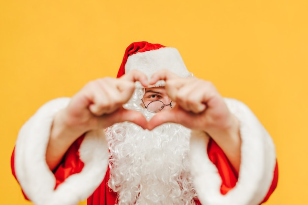 Wesoły święty mikołaj w fantazyjnych goglach pokazuje gest miłości