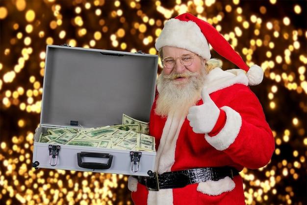 Wesoły święty mikołaj z walizką pieniędzy.
